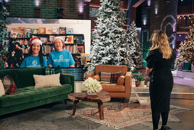 Maureen and Jessica on a big screen TV on set of the Kelly Clarkson Show decorated for the holidays